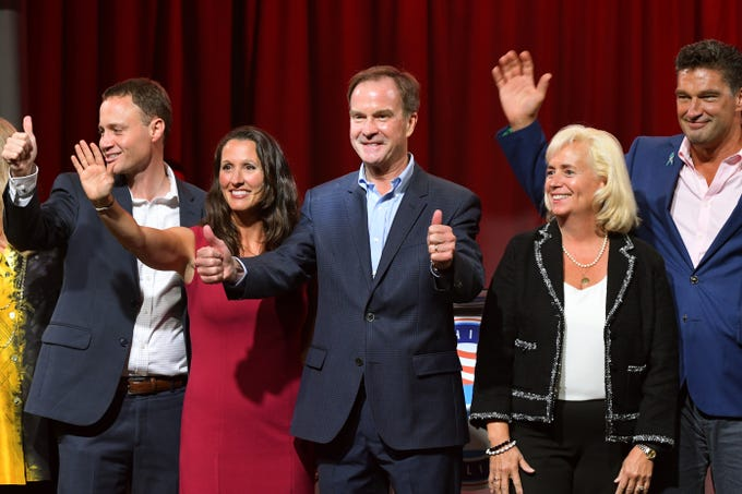 Michigan State GOP candidates Tom Leonard, Lisa Posthumus-Lyons, Bill Schuette, Mary Treder Lang and Dave Dutch, left, to right, celebrate onstage together at the conclusion of the 2018 Republican State Convention in Lansing Saturday August 25, 2018.
