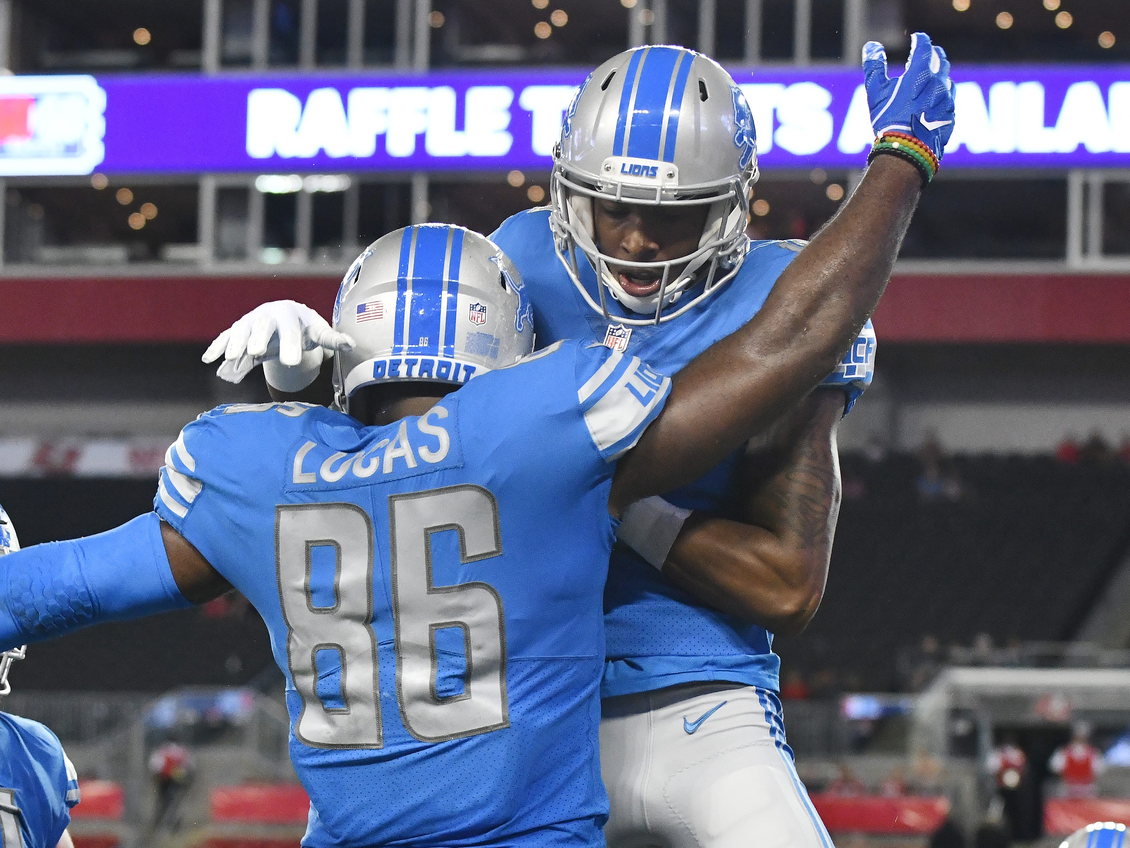 Lions' Marcus Lucas celebrates with Teo Redding and teammates after running in the go ahead touchdown in the fourth quarter.