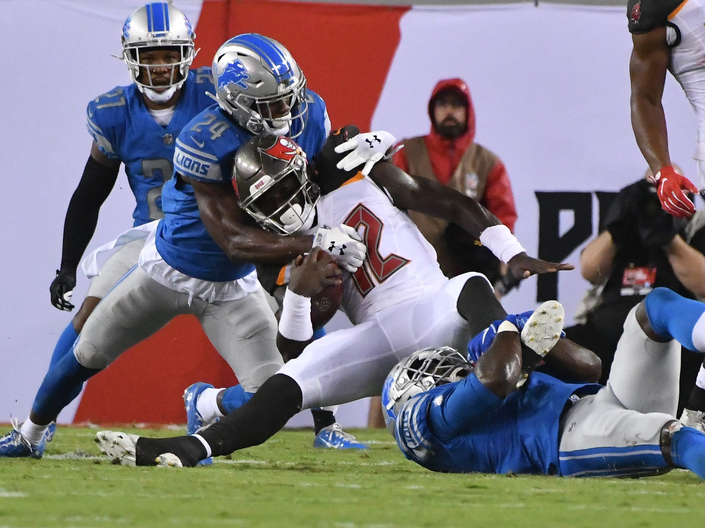 LIons' Nevin Lawson and Christian Jones brings down Buccaneers' Chris Godwin in the first quarter.