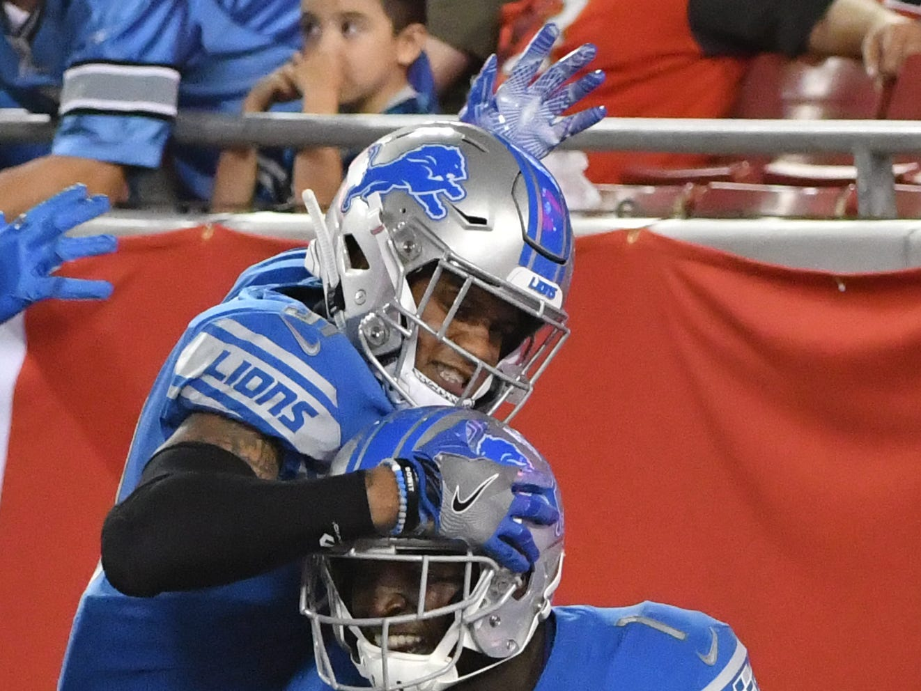 Lions' Teez Tabor celebrates with Brandon Powell after Powell runs a punt back to the end zone for a touchdown in the fourth quarter.