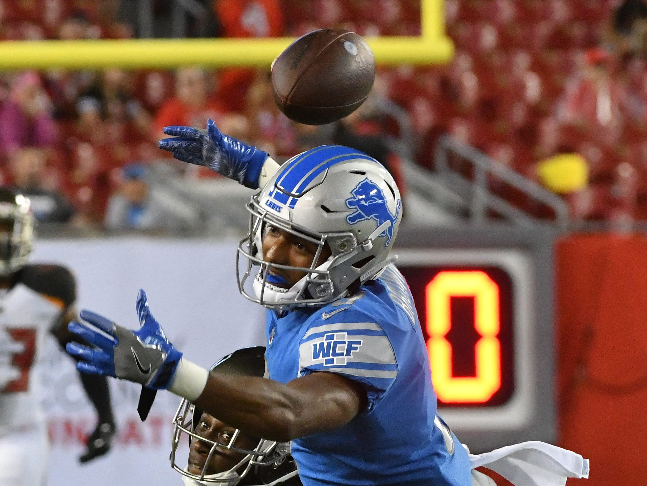 Lions' Brian Brown can't pull in a reception with Buccaneers' De'Vante Harris defending in the fourth quarter.