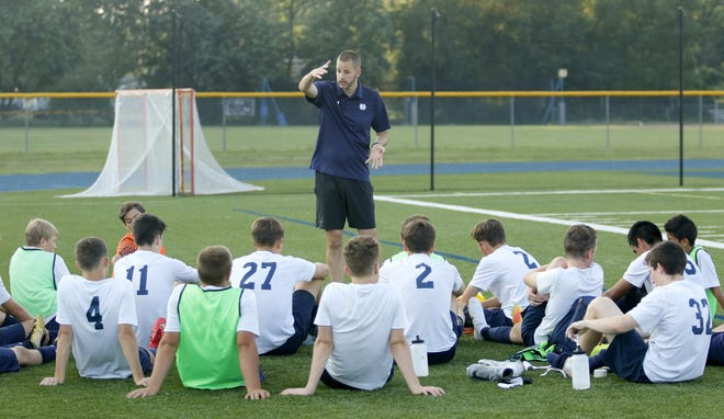 First-year Elmira Notre Dame coach Adam Robinson talks to his team at halftime of a scrimmage against Horseheads on Aug. 24 at Brewer Memorial Stadium.