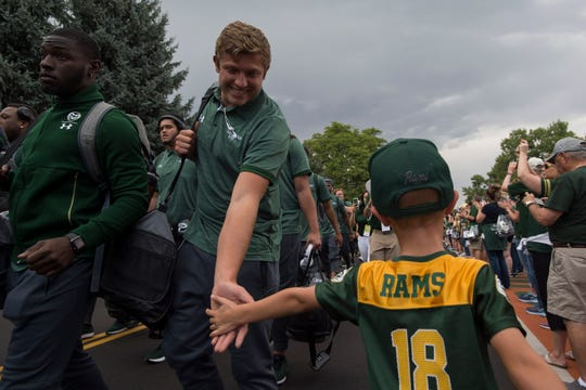 Colton Reynolds, 6, gets a high five from Colorado State University players during the Ram Walk before a game against the University of Hawaii Rainbow Warriors on Saturday, Aug. 25, 2018, at Canvas Stadium in Fort Collins, Colo.