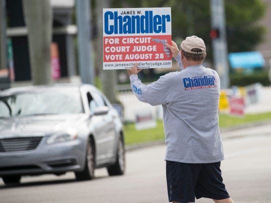 Voters are greeted by people campaigning for candidates on Saturday, the final day of early voting in Lee County.