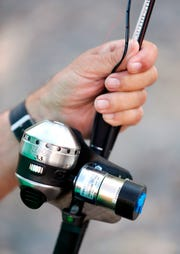 This photo taken Aug. 7. 2018, shows Larry Rennich, who has the use of only one arm after a stroke, holding a motorized fishing reel made by this friend Frank Ewalt.  Although Ewalt is still tinkering with making the setup better, he's managed to modify a Zebco 33 reel so that a small 3 milli-amp motor powered by batteries can reel in the fishing line with the push of a button.(Casey Page /The Billings Gazette via AP)