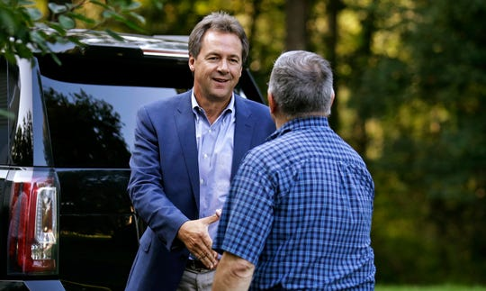 Montana Gov. Steve Bullock, left, shakes hands with a guest as he arrives for a house party supporting Democratic candidates in Hampton, N.H., Friday, Aug. 24, 2018. Bullock is visiting New Hampshire this weekend as he explores a possible 2020 presidential bid. (AP Photo/Charles Krupa)