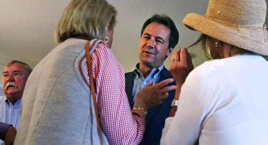 Montana Gov. Steve Bullock, center, listens to guests as he attends a house party supporting Democratic candidates in Hampton, N.H., Friday, Aug. 24, 2018. Bullock is visiting New Hampshire this weekend as he explores a possible 2020 presidential bid. (AP Photo/Charles Krupa)