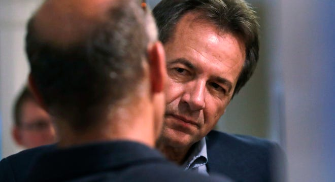 Montana Gov. Steve Bullock listens to a guest as he attends a house party supporting Democratic candidates in Hampton, N.H., Friday, Aug. 24, 2018. Bullock is visiting New Hampshire this weekend as he explores a possible 2020 presidential bid. (AP Photo/Charles Krupa)