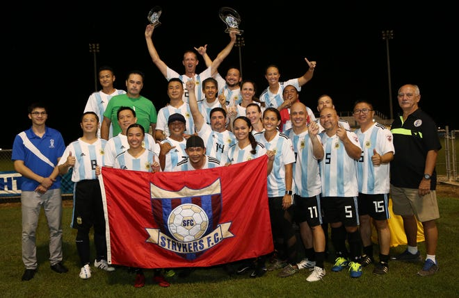 The Bank of Guam Strykers Masters pose with the champions trophy of the 2018 Bud Light Co-Ed Masters Soccer League following the team's 1-0 victory in the title match against the NAPA Rovers Masters Friday at the Guam Football Association National Training Center.