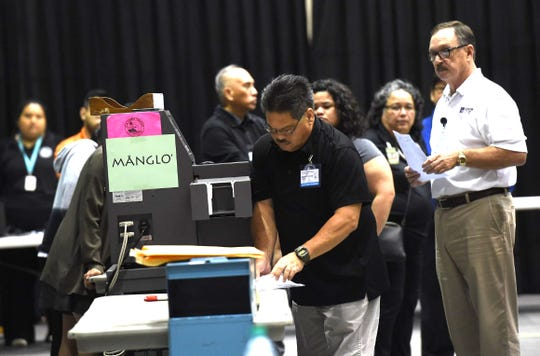 Election officials begin tabulating the first batch of ballots in the Primary Election at the University of Guam on Aug. 25, 2018.