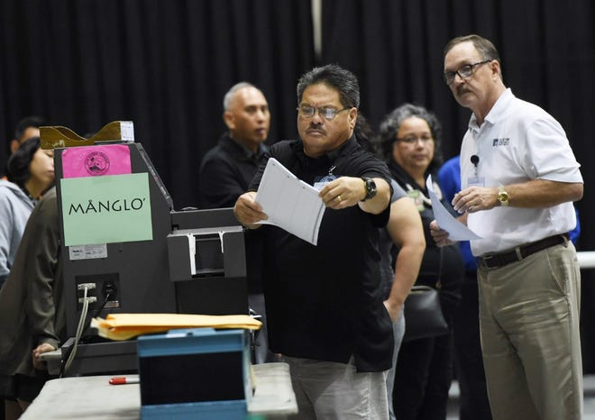 In this Aug. 25 file photo, election workers begin tabulating the first batch of ballots at the University of Guam Calvo Field House.