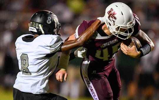 North's James Butler (8) tries to pull down Henderson's Ian Pitt (45) as the Evansville North Huskies play the Henderson County Colonels at Colonel Field Friday, August 24, 2018.