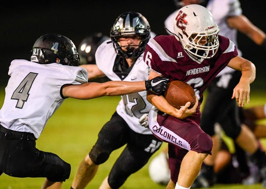 Henderson's Logan Green (6)  splits the defense from North's Trevor Rumsey (4) and McCoy Walters (12) as the Evansville North Huskies play the Henderson County Colonels at Colonel Field Friday, August 24, 2018.