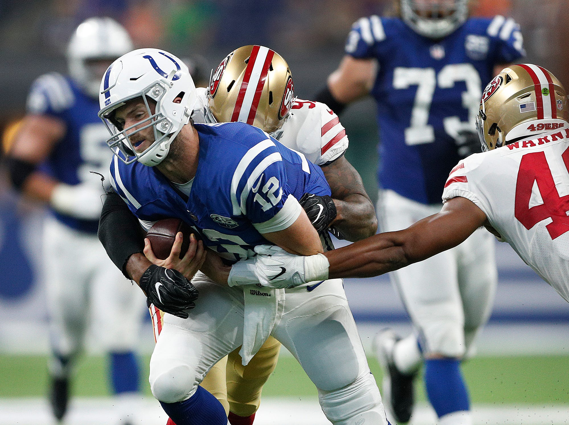 Indianapolis Colts quarterback Andrew Luck (12) is tackled by San Francisco 49ers linebacker Dekoda Watson (97) after running for a first down in the first half of their preseason football game at Lucas Oil Stadium Saturday, August 25, 2018.