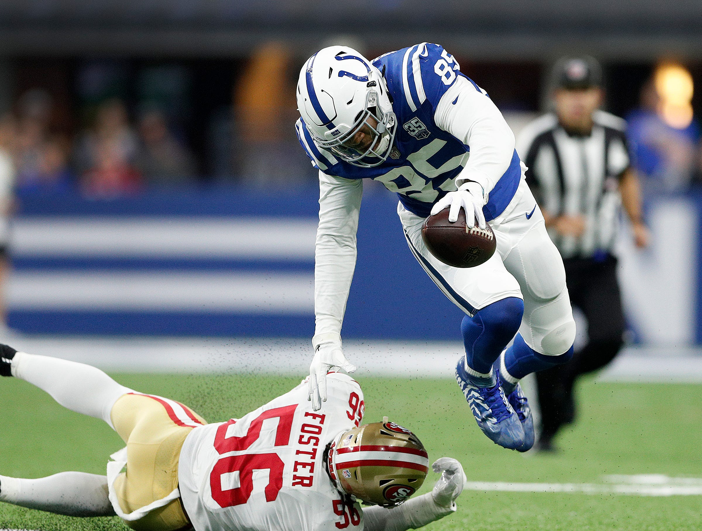Indianapolis Colts tight end Eric Ebron (85) attempts to avoid the tackle by San Francisco 49ers linebacker Reuben Foster (56) in the first half of their preseason football game at Lucas Oil Stadium Saturday, August 25, 2018.