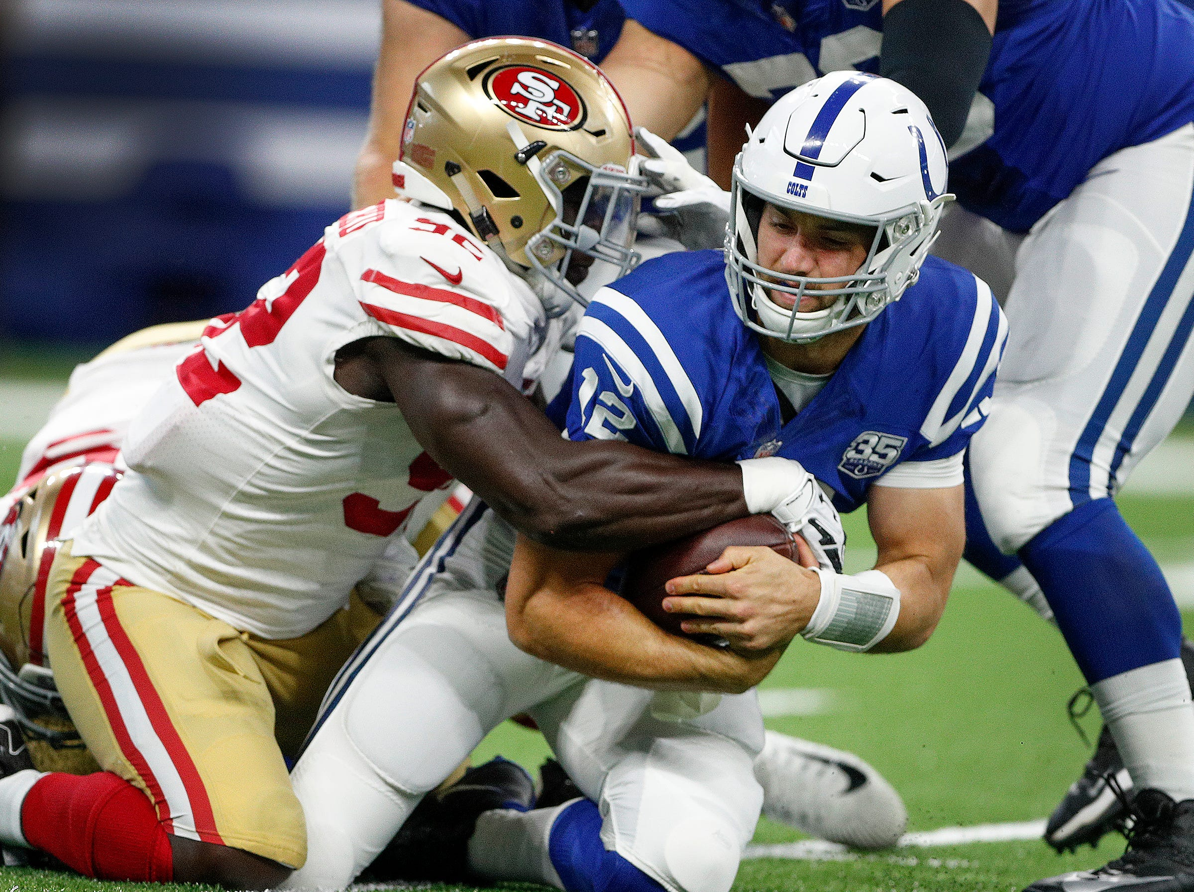 Indianapolis Colts quarterback Andrew Luck (12) is sacked by San Francisco 49ers defensive end Jeremiah Attaochu (92) in the first half of their preseason football game at Lucas Oil Stadium Saturday, August 25, 2018.