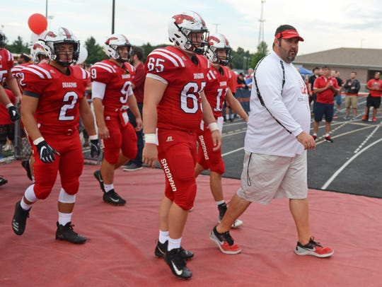 New Palestine head coach Kyle Ralph walks onto the field with his team to take on Center Grove at New Palestine High School in New Palestine, Ind., Friday, Aug. 24, 2018. The New Palestine Dragons defeated the Center Grove Trojans 31-9.