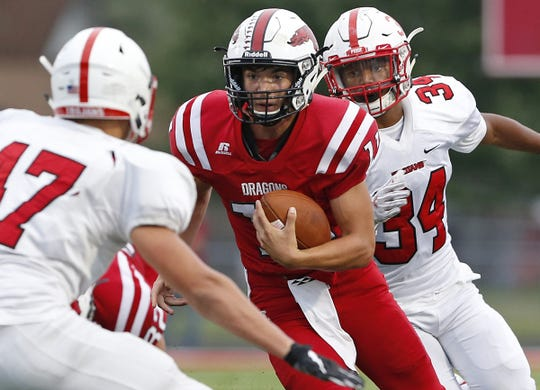 New Palestine quarterback Zack Neligh runs the ball through Center Grove defenders in the first half of the game at New Palestine High School in New Palestine, Ind., Friday, Aug. 24, 2018. The New Palestine Dragons defeated the Center Grove Trojans 31-9.
