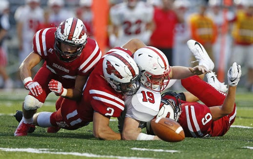 Center Grove tight-end Cam Petty scuffles against New Palestine defenders for a loose ball in the first half of the game at New Palestine High School in New Palestine, Ind., Friday, Aug. 24, 2018. The New Palestine Dragons defeated the Center Grove Trojans 31-9.