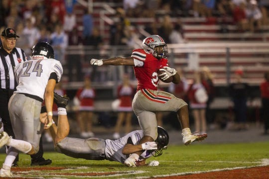 Iowa City High's Tonka Hickman sheds a tackle past the 50 on a touchdown run during a football game on Friday, Aug. 24, 2018, at Bates Field in Iowa City.