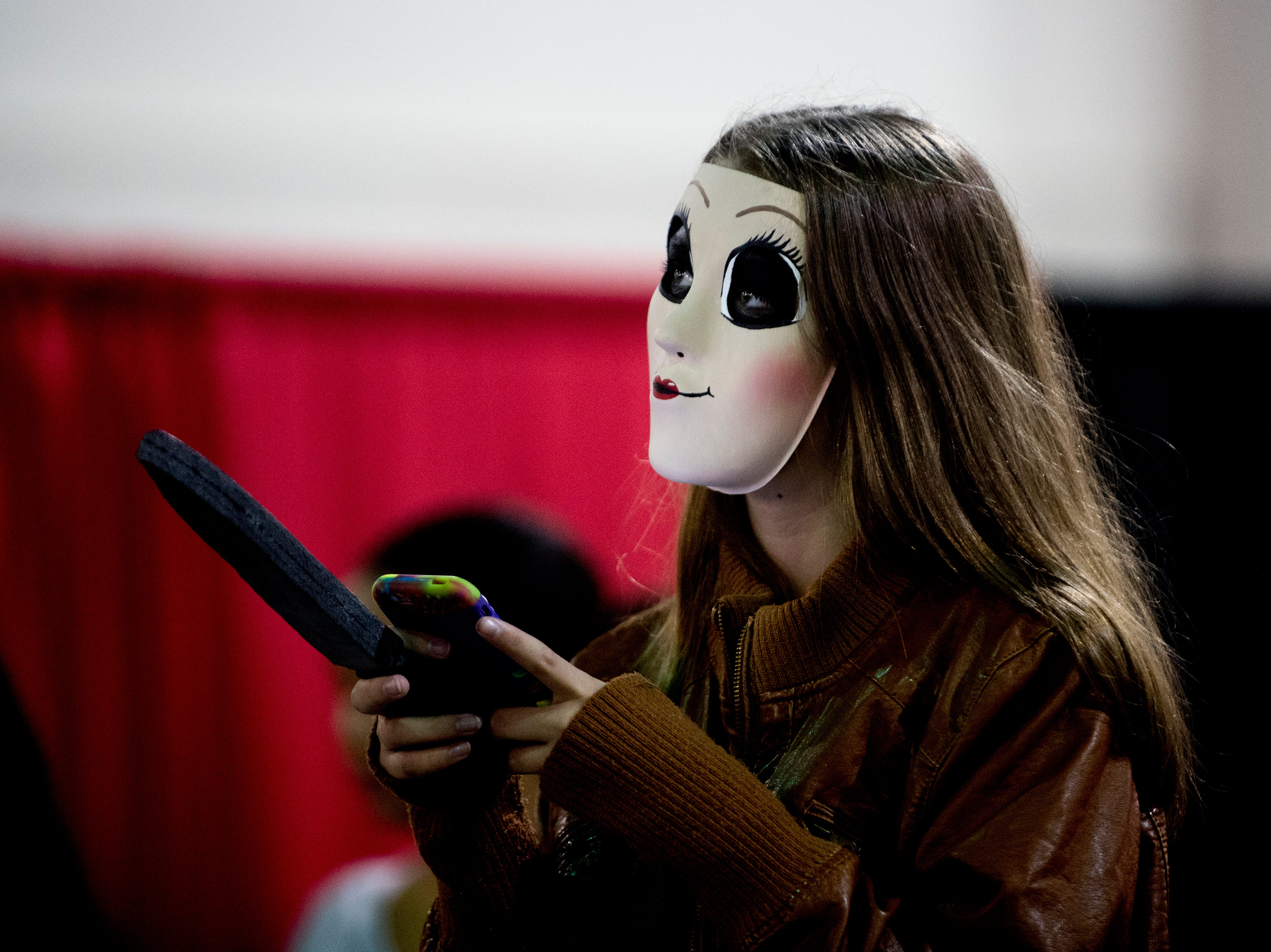 An attendee looks up from their phone during the annual Knoxville CreepyCon at the World's Fair Exhibition Hall in Knoxville, Tennessee on Saturday, August 25, 2018. The event featured performers, a zombie beauty contest, workshops and a wide selection of vendors.