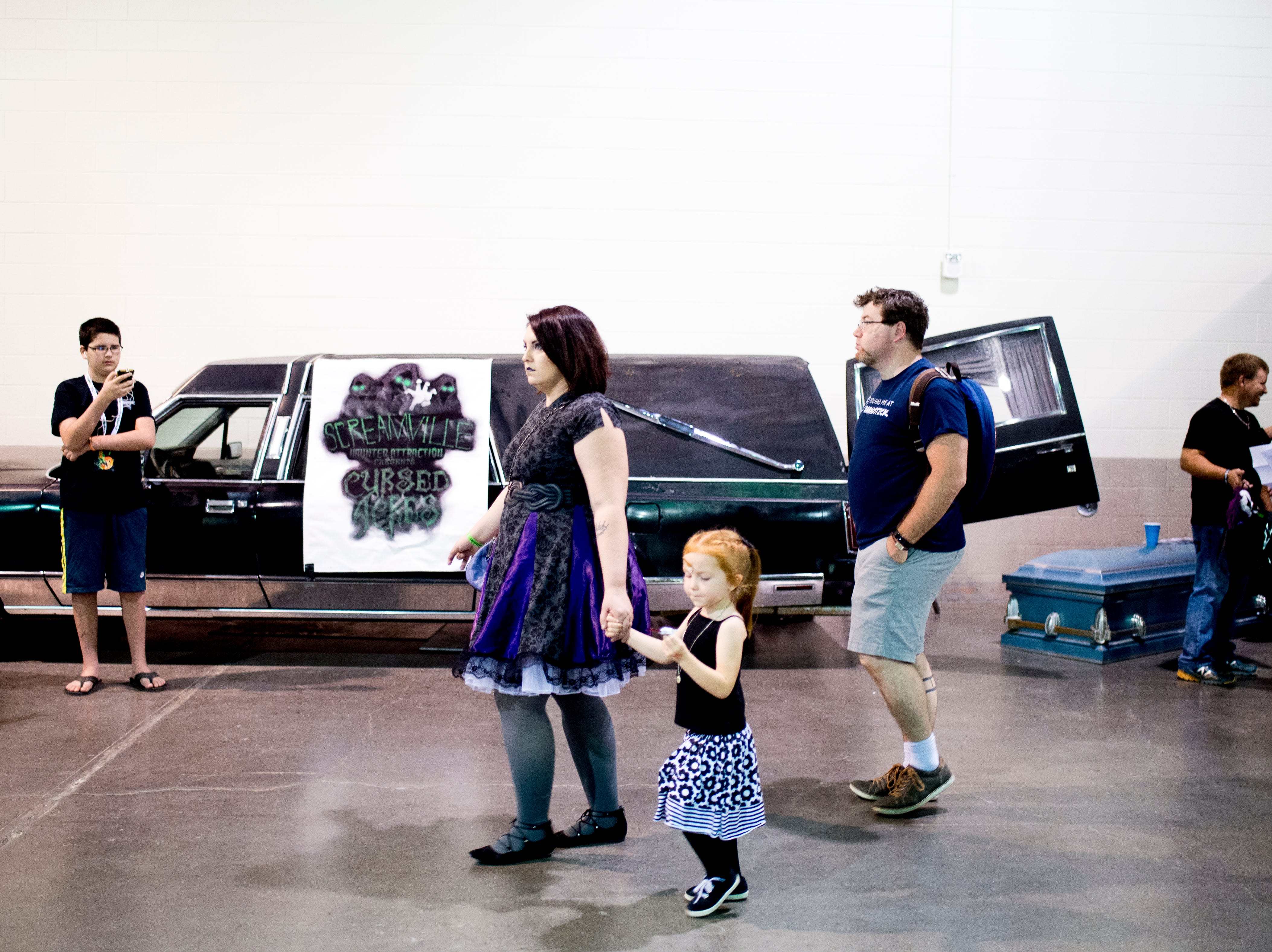 Visitors walk by a vintage hearse during the annual Knoxville CreepyCon at the World's Fair Exhibition Hall in Knoxville, Tennessee on Saturday, August 25, 2018. The event featured performers, a zombie beauty contest, workshops and a wide selection of vendors.