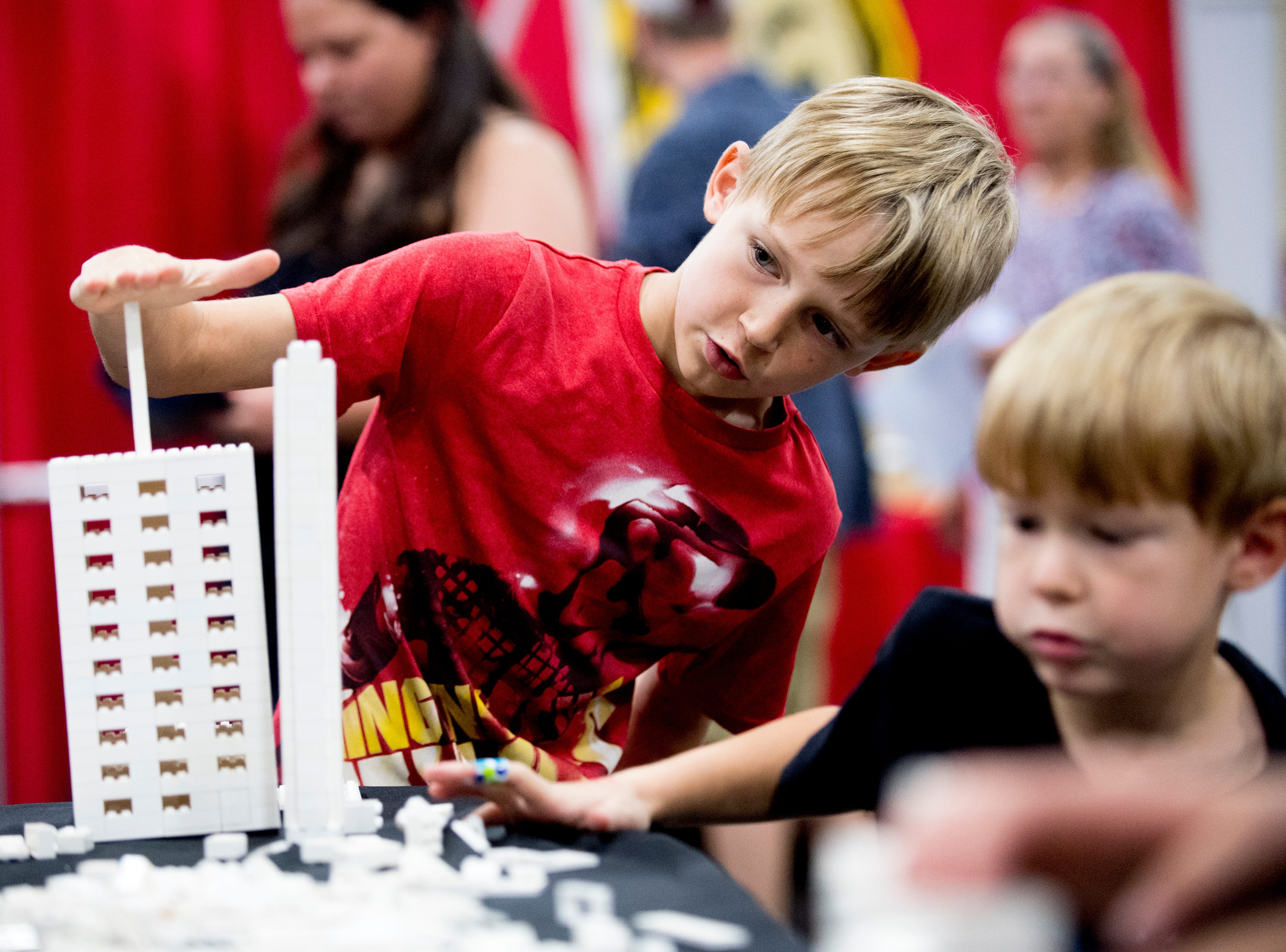 bryce Bolin, 8, of Knoxville, and his brother Blake, 5, build Lego towers at the BrickUniverse Knoxville LEGO Fan Expo in the Knoxville Convention Center in Knoxville, Tennessee on Saturday, August 25, 2018. Life-sized LEGO displays, over 40 world landmarks build to-scale from LEGO as well as castles, trains, and cities and other creations were on display.