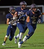 Central Catholic's Preston Hensley and Scott Lovell flank junior Daniel Roach as he drives downfield against the Golden Eagles Friday night.