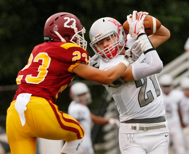 Harrison Truitt of West Lafayette with a pass reception in front of Clint Garriott of McCutcheon in the first quarter Friday, August 24, 2018, in Lafayette.