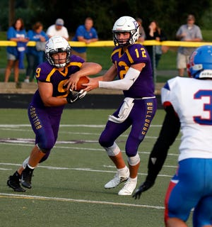 Bloom-Carroll junior quarterback Otto Kuhns hands the ball off to sophomore running back Hobie Scarberry during the Bulldogs' season opener against Highland. The Bulldogs are averaging 42.1 points per game and are 2-0 on the season.