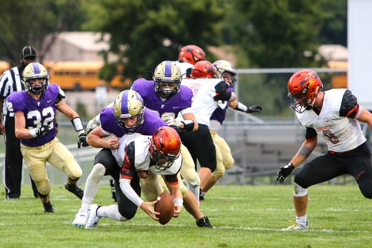 Fowlerville's Tom Salois tackles Charlotte quarterback Dominic Ghiardi after a fumbled handoff on Friday, Aug. 24, 2018.