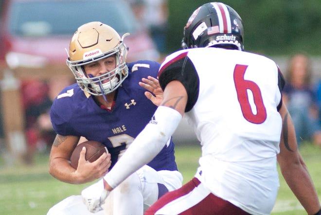 Male quarterback Garrett Dennis puts out an arm for Ballard linebacker Jared Casey.  August 24, 2018