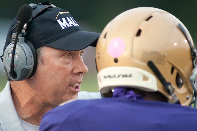 Male head football coach Chris Wolfe talks to running back Jaylin Bross during the game.