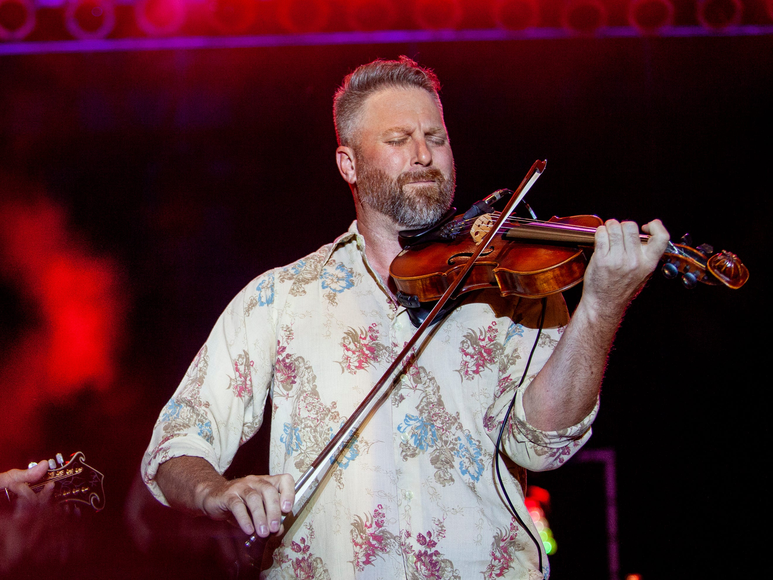 Josh Turner (left) smiles as his fiddle player takes the lead at the Kentucky State Fair on Friday, August 24, 2018.