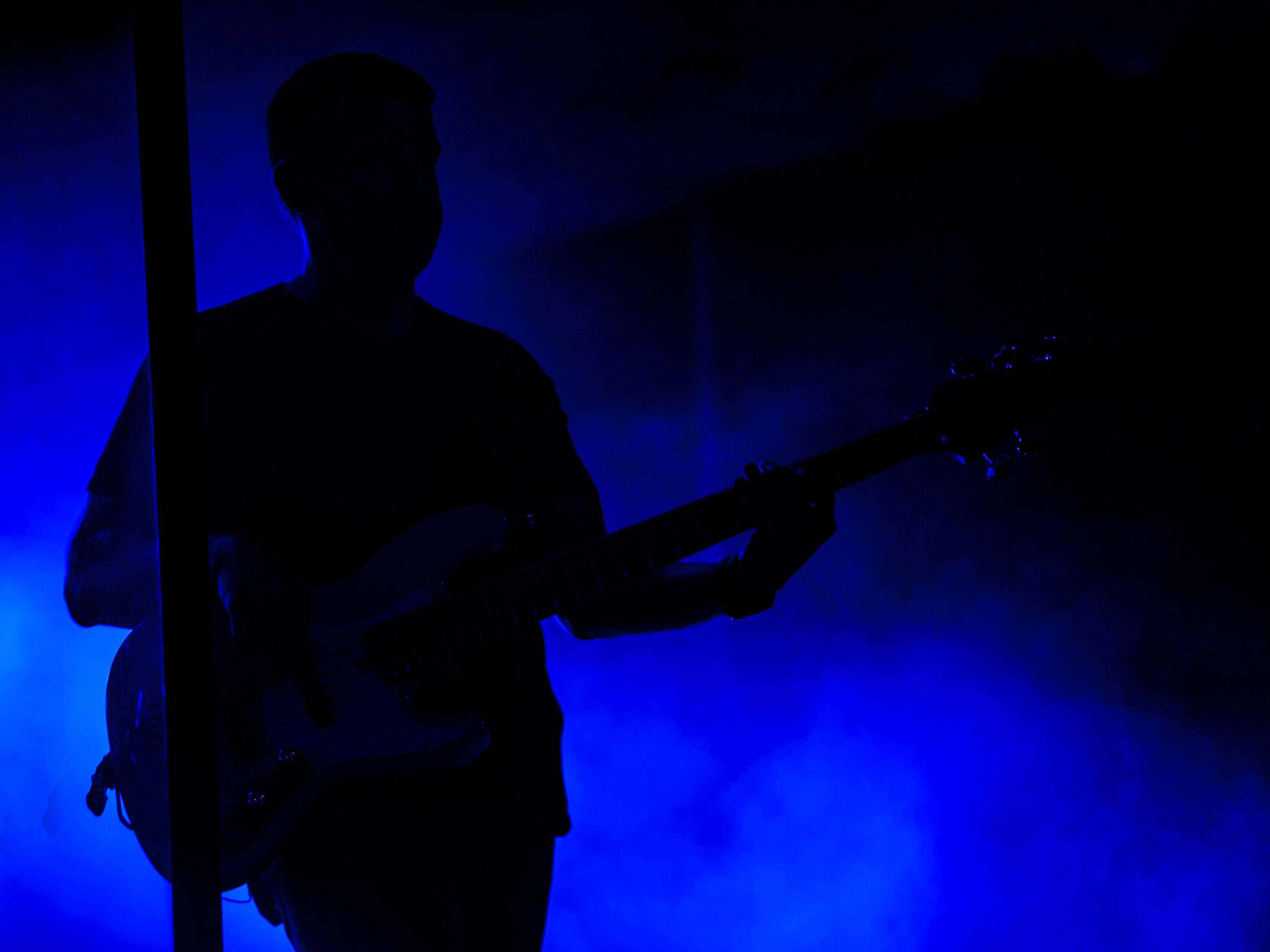 The bass player in Josh Turner's band is seen in silhouette and blue light at the Kentucky State Fair. August 24, 2018