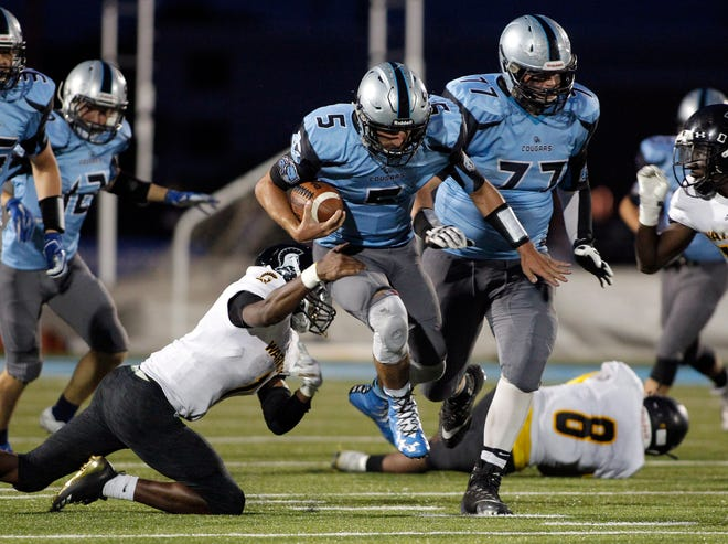 Lansing Catholic quarterback Josh Kramer (5) gets away from Waverly's Devin Johnson on a keeper, Friday, Aug. 24, 2018, in Lansing, Mich. Lansing Catholic won 42-0.