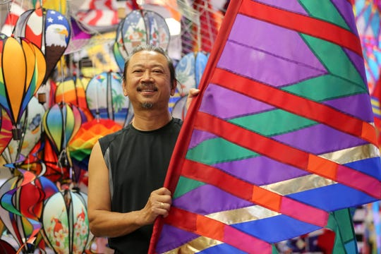 Chow Chong, owner of Unique Flying Objects, poses with a colorful kite at his store Tuesday, August 7, 2018, in Two Rivers, Wis. Chong is the founder and organizer of Two Rivers' annual Kites Over Lake Michigan festival.  Josh Clark/USA TODAY NETWORK-Wisconsin