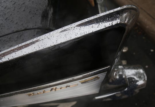 The fin of a 1957 Chevy Bel Air collect rain droplets during the Heart of the City Cruise on Saturday.