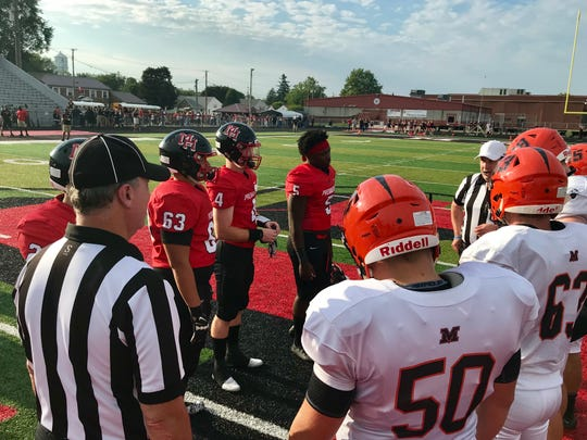 Marion Harding's football captains meet Mount Vernon and the officials at midfield for the coin toss before Friday night's season opener at Harding Stadium. Harding won 21-12.
