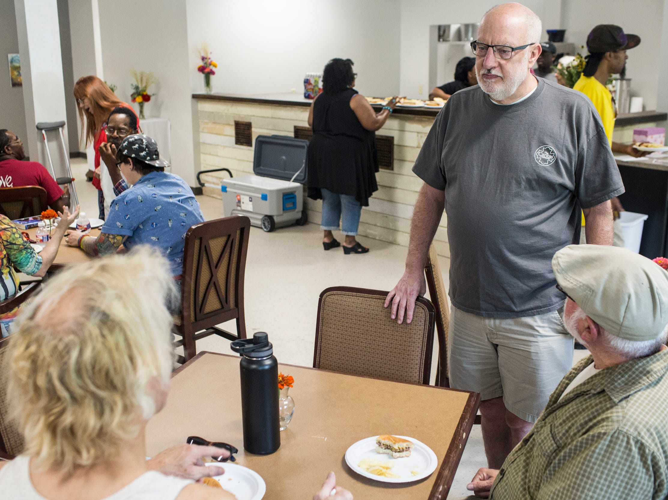 August 25 2018 - Mac Edwards, the new executive director of Caritas Village, center, talks with guests during a get together at the re-opened Caritas Village.