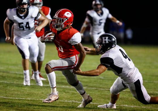 Germantown receiver Cameron Baker (left) runs out a tackle by Houston defender Lincoln Pare (right) during action of their prep football game in Germantown.
