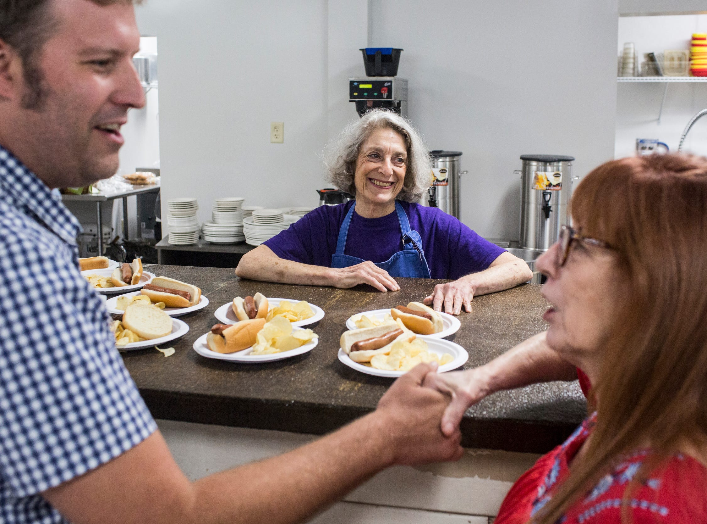 August 25 2018 - Eddie Thomas, center, smiles while serving food during a get together at the re-opened Caritas Village.