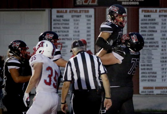 Joseph Mlachnik gets hoisted into the air by teammate Jacob Leszczynski after scoring the Warriors' second touchdown of the game against Arrowhead on Friday night.