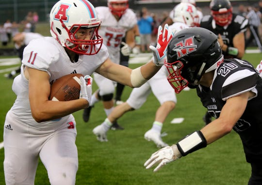 Arrowhead's Jacob Schleicher tries to ward off Muskego's Sam Chovanec with a stiff arm Friday night.