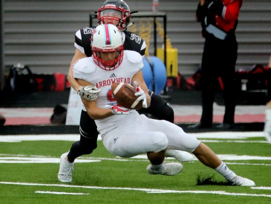 Arrowhead receiver Roby Symdon hauls in a pass despite tight coverage by Muskego's Joseph Mlachnik at Muskego on Aug. 24.