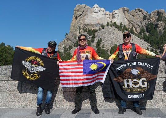 Harley drivers from Cambodia Shyan Low (left), Sean Wong and Kohor Hock pose for a picture Saturday at Mount Rushmore National Memorial at Keystone, S.D. They take part in Harley's Rides Home for the 115-year anniversary celebration of the motor manufacturer in Milwaukee. They are Malaysian citizens who live in Cambodia. Wong (middle) holds a Malaysian flag.