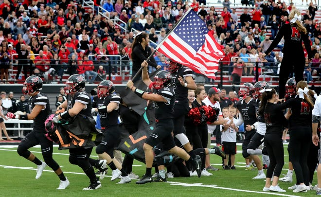 The Muskego football team charges on to the field for its game at home against Arrowhead on Friday night. The No. 2-ranked Warriors ended up with a 42-30 victory over the Warhawks.