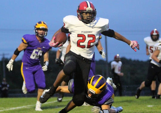 Pewaukee running back Kris Johnson tries to escape the grasp of New Berlin Eisenhower's Nate Clark on August 24.