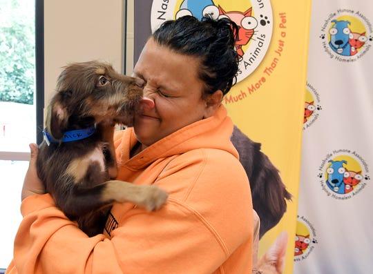Leann Beckham holds a puppy called Yannick Weber — named after the Nashville Predators' defenseman. Beckham adopted the dog during Mars Petcare's adoption weekend event at Nashville Humane Association on Saturday, August 25, 2018.