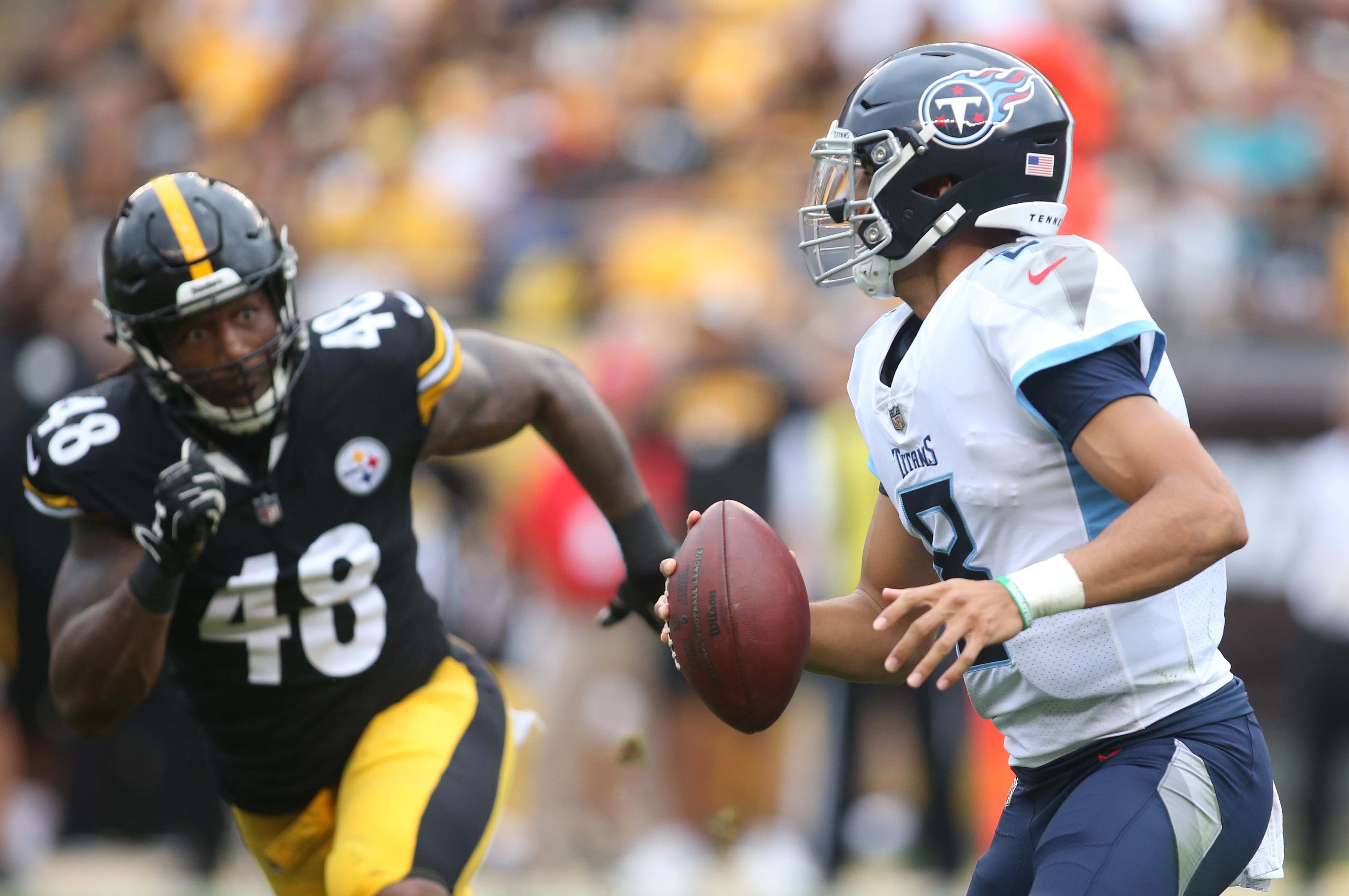 Tennessee Titans quarterback Marcus Mariota (8) scrambles with the ball as Pittsburgh Steelers linebacker Bud Dupree (48) pressures on Aug. 25, 2018.